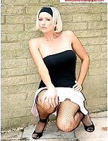 Lucy In Black Fishnets And Mini Skirt By A Wall