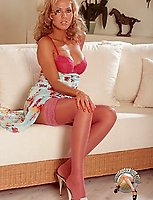Long legged pornstar undresses and poses in pink lingerie and stockings