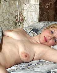A horny mature blond plays with dildo on the bed