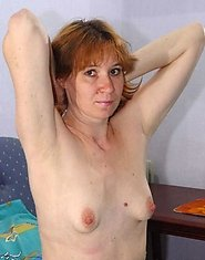 Fine mature redhead teacher undresses in front of a mirror